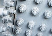 stock photo of bolt  - Gray painted metal surface with bolts and hexagon nuts - JPG