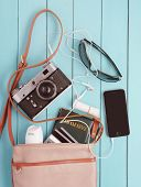 stock photo of blue things  - female bag with a variety of personal belongings and with retro camera - JPG