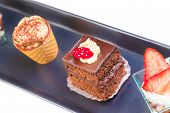 pic of fancy cakes  - top of view of delicious chocolate cake near little cakes on black dish - JPG