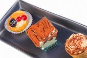 image of fancy cakes  - top of view of delicious tiramisu cake near little cakes on black dish - JPG