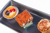 stock photo of fancy cake  - top of view of delicious tiramisu cake near little cakes on black dish - JPG