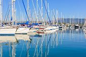 foto of sloop  - Panorama of a big Gouvia harbour with white yachts and boats on a beautiful sunny day over the island of Corfu - JPG