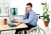 stock photo of workplace accident  - man in wheelchair is working in the office - JPG