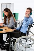 stock photo of workplace accident  - man in wheelchair and his is female colleague working in the office - JPG