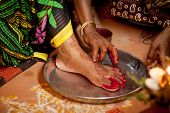 pic of pooja  - Indian bride doing marriage rituals doing colored foot fingure their mandap puja - JPG