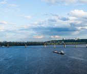 stock photo of sloop  - The barge floating in the blue Dnieper waters against the summer Kyiv landscape - JPG