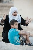 stock photo of arabic woman  - Arabic Muslim Middle Eastern poor woman with her son on dirty ground - JPG