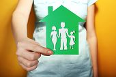 stock photo of social housing  - Cutout house with paper family in female hand on colorful background - JPG
