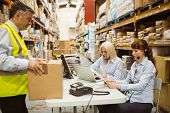 picture of warehouse  - Warehouse team working together on shipment in a large warehouse - JPG