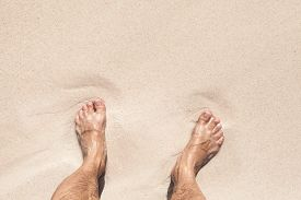 picture of wet feet  - Wet male feet stand on white coastal sand - JPG