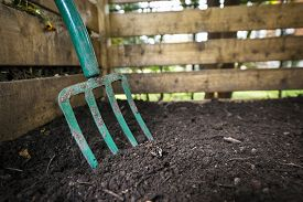 stock photo of decomposition  - Garden fork turning black composted soil in wooden compost bin - JPG