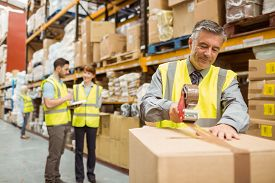 foto of warehouse  - Warehouse worker sealing cardboard boxes for shipping in a large warehouse - JPG