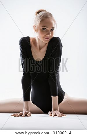 Graceful ballerina in black leotard doing stretching