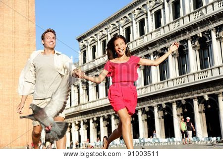 Couple in love having playful fun in Venice travel holding hands running laughing in Venice, Italy on Piazza, San Marco. Happy young couple on travel vacation on St Mark's Square. Happy woman and man.