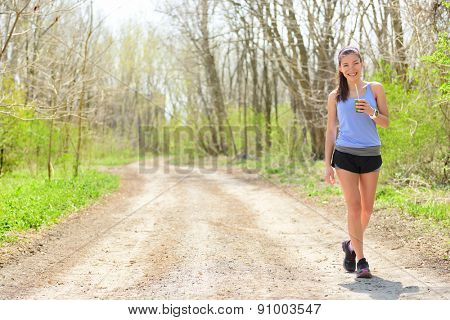 Woman runner drinking green smoothie wearing smartwatch. Female runner resting drinking a spinach and vegetable smoothie taking a break walking and resting during outdoor running workout in forest.