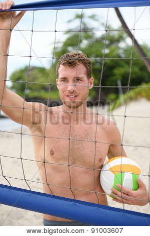 Beach volleyball man in sporty healthy lifestyle portrait holding volley ball after game on summer beach. Handsome topless shirtless male fitness model living active lifestyle doing sport on beach.