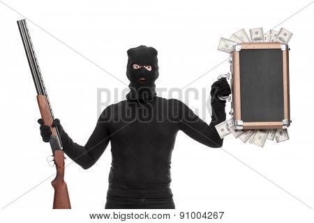 Masked criminal holding a briefcase full of money in one hand and a shotgun rifle in the other isolated on white background