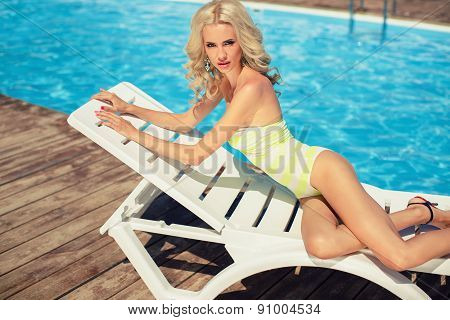 Woman relaxing on a lounger by the pool