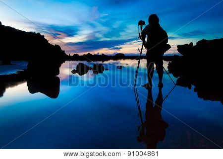 Silhouette of Photographer taking sunset/sunrise with reflection