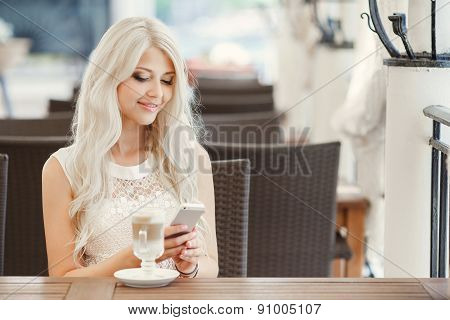 Portrait of beautiful girl using her mobile phone in cafe.