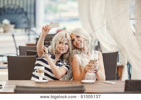 Beautiful friends are watching on smartphone and drinking coffee in a cafe.