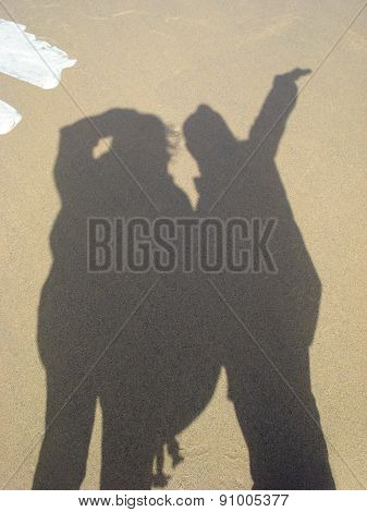 shadow of two people on a beach