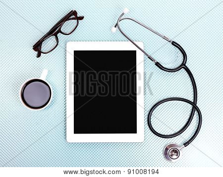 Medical tablet, stethoscope, glasses and coffee cup on blue background