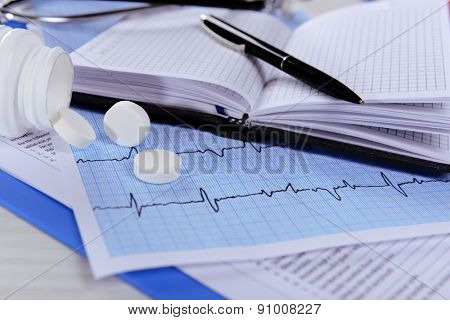Cardiogram with pills on table, closeup