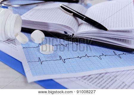 Cardiogram with pills on table, closeup