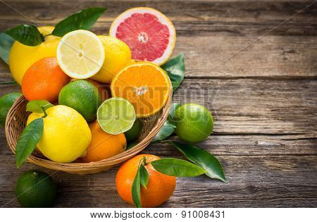 Fresh and juicy citrus fruits in the basket on the rustic table