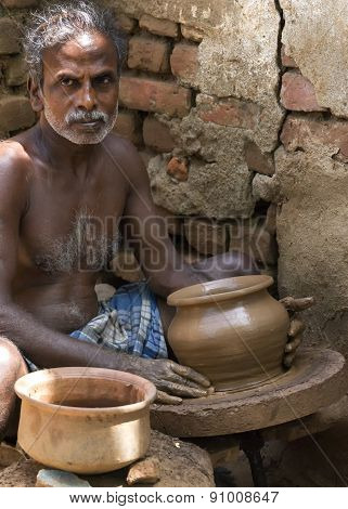 Pot Maker At His Turning Table With Finished Product.