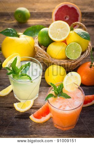 Two glasses with cold lemonade made of lemon and grapefruit