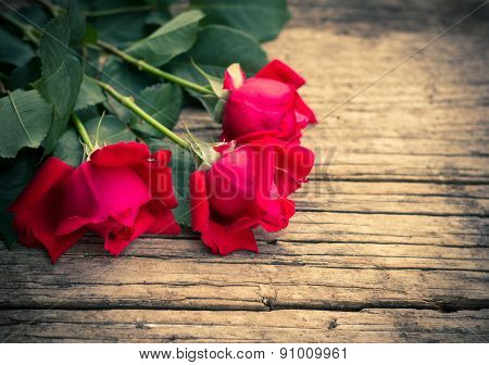 Red roses on the rustic wooden background