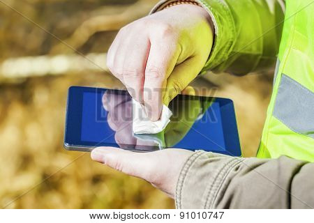Close up of man hand with wipe on tablet PC