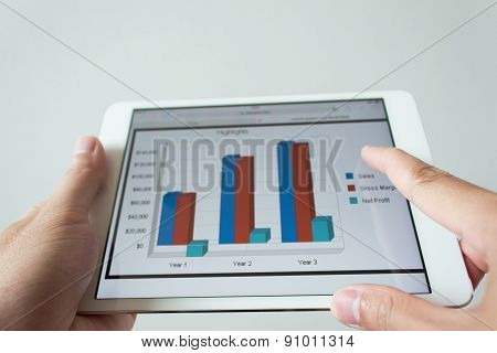 Businessman Hand Touching Screen Of Tablet Computer With Market Graph