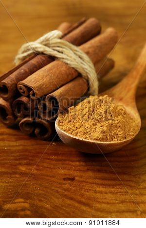 fragrant cinnamon sticks and ground spices on a wooden background
