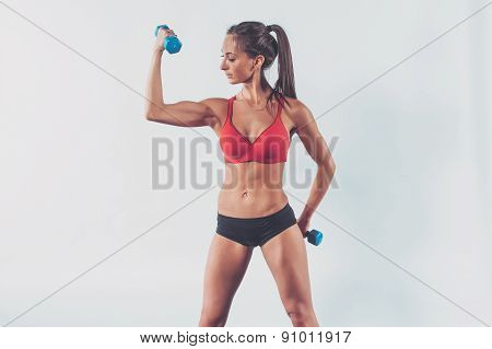athletic woman pumping biceps doing workout lifting up dumbbell exercise for arm muscles fitness, sp