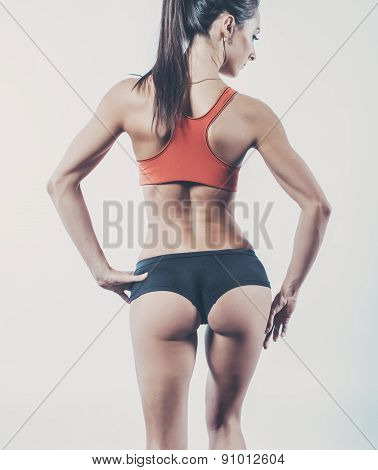 Muscular active athletic young woman with sexy buttocks posing showing muscles of the back shoulders
