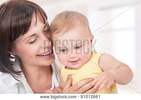 Closeup portrait of beautiful cheerful mother having fun with adorable little daughter at home, happy motherhood concept