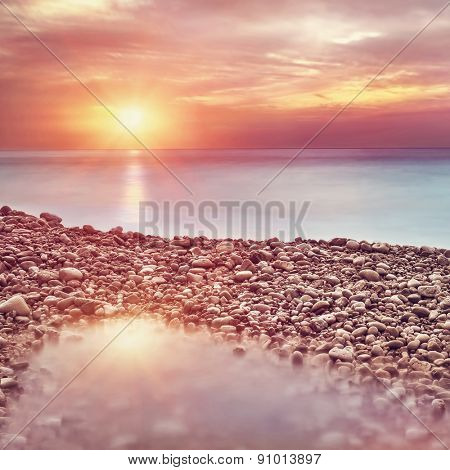 Beautiful beach landscape in sunset light, amazing view on pebble coastline, romantic travel destination