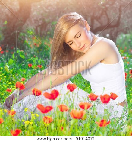 Beautiful woman with closed eyes sitting on poppy flower field, relaxation outdoors on fresh gentle floral meadow, enjoying spring nature
