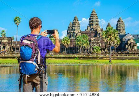 Young man taking photo of Angkor Wat, Cambodia
