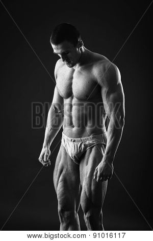 Young bodybuilder guy in good shape against a dark background