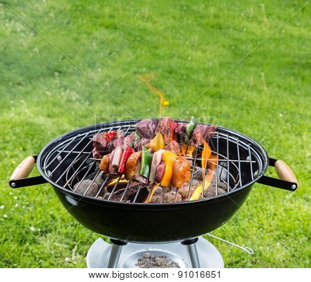 Empty grill with fire flames placed on garden lawn