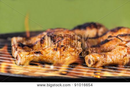 Chicken legs on barbecue grill with fire