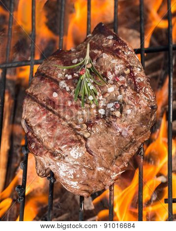 Delicious beef steak on grill with flames