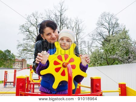 Mom Plays With Her Daughter At The Playground On A Toy Ship