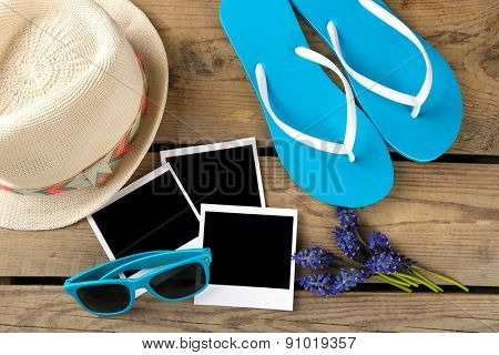 Sunglasses, flip flops and hat wooden background