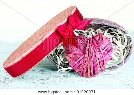Wicker heart in present box on wooden table