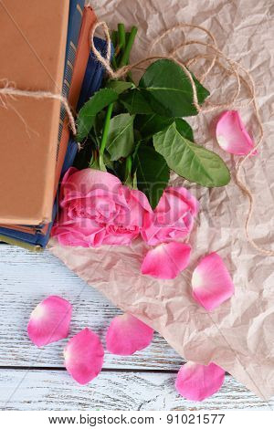 Beautiful pink roses with stack of books on wooden table with parchment, top view